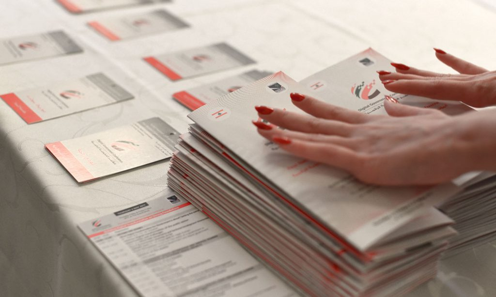 LDG- hands pressing down many brochures designed with brand image in mind